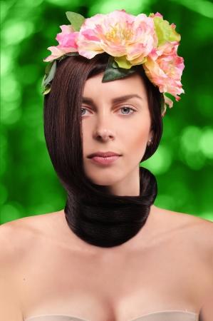 cabelo amarrado: menina linda morena vestindo uma grinalda de rosa tsetov com o cabelo amarrado em um n� em volta do pesco�o em um fundo verde com bokeh