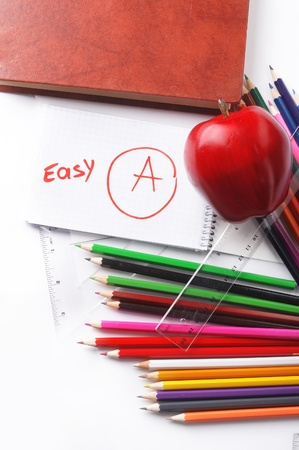 school supplies. book, pencil, notebook, ruler and red apple on a white background photo