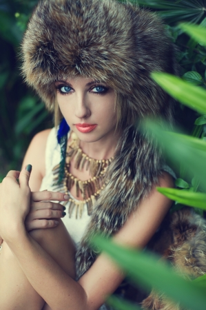 Lady in a fur hat in the jungle, fashion portrait