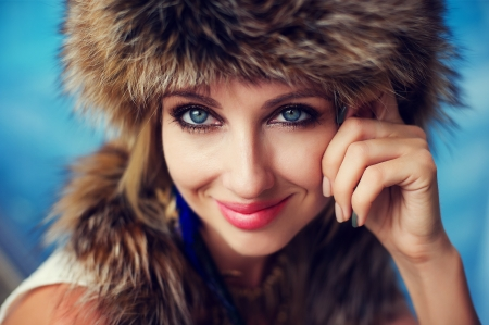 Fashion portrait of a woman in fur next to the swimming pool
