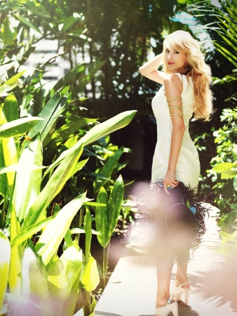 Young blonde woman in white dress in the garden