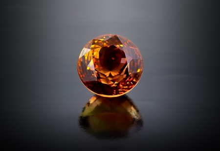 Single round citrine gemstone on dark background  Stock Photo