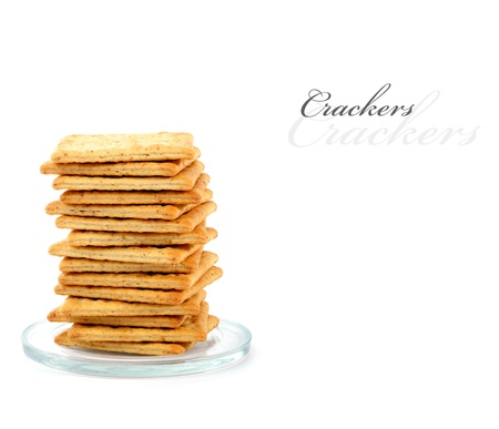 Pile of crackers on a small glass plate,  isolated on white with copy space  Stock Photo