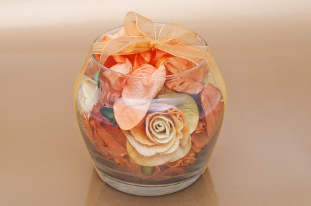 Dried flowers inside transparent glass bowl on beige background. photo