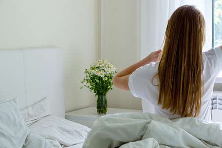 Young pretty girl sitting in bed at home and stretching after wake up.