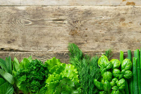 Flat lay of various fresh herbs on old wooden background. Space for text. 版權商用圖片