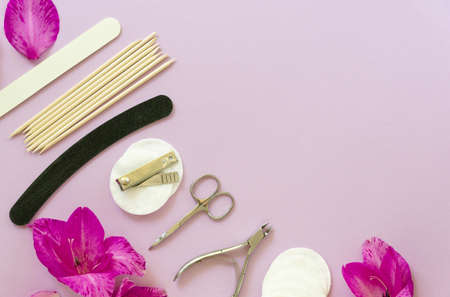 Flat lay of manicure accessories with flowers on a lilac background. Space for text