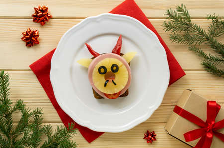 Funny sandwich with sausage, pineapple and vegetables in the shape of a bull. Festive breakfast or lunch for kids. Symbol of the new year 2021