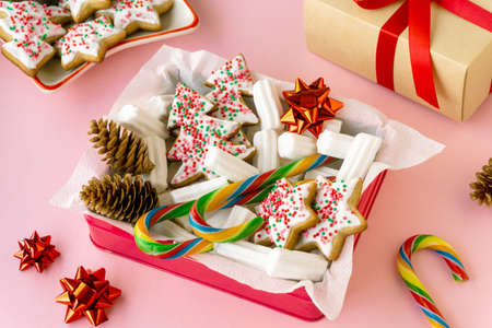 Christmas or new year gift box with gingerbread cookies, marshmallows and lollipops on a pink background.