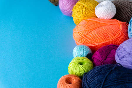 Various colored balls of yarn on a blue background. Threads for crocheting and knitting.
