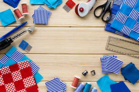 Items for patchwork. Pieces of fabric and sewing accessories on a wooden background. Space for text. Stockfoto