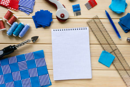 Items for patchwork. Pieces of fabric, sewing accessories and blank notebook on a wooden table. Stockfoto