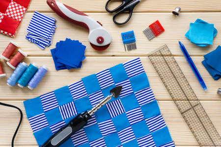 Process of making patchwork quilt. Sewing accessories and fabric pieces on a wooden background.