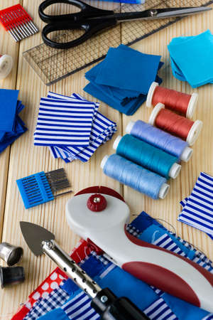 Items for patchwork. Pieces of fabric and sewing accessories on a wooden background.