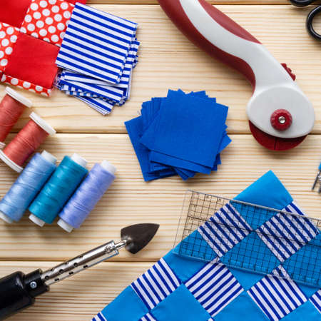 Items for patchwork. Pieces of fabric and sewing accessories on a wooden background. Stockfoto