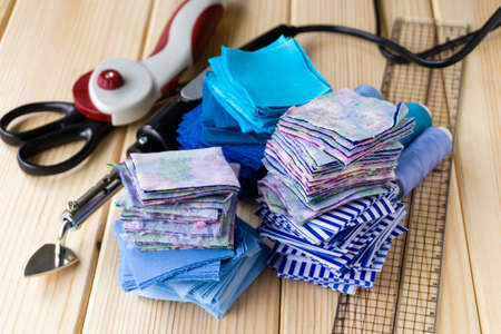 Stack of fabric pieces and patchwork accessories on a wooden background.