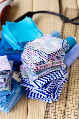 Stack of fabric pieces for patchwork on a wooden background. Stockfoto