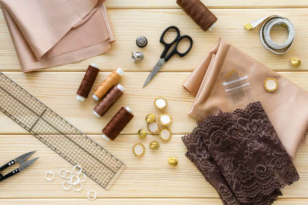 Flat lay of sewing accessories. Cloth, threads and tailoring tools on wooden background.