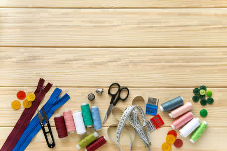 Flat lay of accessories for tailor. Set of sewing supplies on wooden background, space for text.
