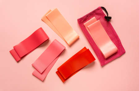 Flat lay of pink fitness bands on colored background, top view