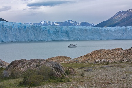view from the coast of Lake Argentino on the boat floating before a glacier of Perito Moreno Stock Photo