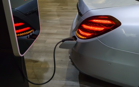 Silver electric car with a plugged in power cable at charging station. Concept of electrical mobility and environmet friendly transportation.