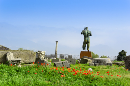 Pompeii ruins and bronze statue of Daedalus by Igor Mitoraj among poppies and green grass. Archaeological site of ancient Pompeii town destroyed by eruption of volcano Vesuvius, Italy