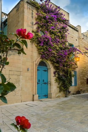 Mdina, Malta: traditional Maltese house with artistic doors, bright flowers of purple bougainvillea on the limestone wall and lantern lights