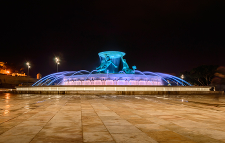 Triton Fountain in Valletta, Malta with flowing water and colorful illumination at night
