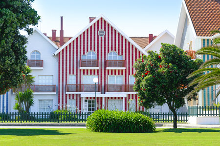 Cozy colorful striped house with red and white stripes in countryside, lawn and blossoming tree with red flowers. Costa Nova, Portugal. Stock fotó