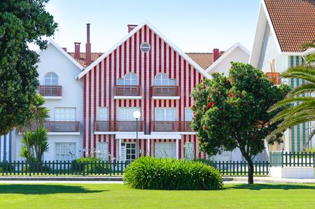 Gemütliches bunt gestreiftes Haus mit roten und weißen Streifen in Landschaft, Rasen und blühendem Baum mit roten Blumen. Costa Nova, Portugal. Standard-Bild