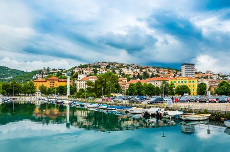 Rijeka, Croatia: View from Rjecina river over the city of Rijeka with Liberation Monument and boats in front and colorful buildings and Trsat castle on the hill in the background