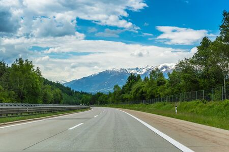Autobahn or highway in the mountains with clear marking surrounded by vibrant green trees under blue sky. Stunning view and a snow-covered mountain in the background. The Alps, Austria Stock Photo
