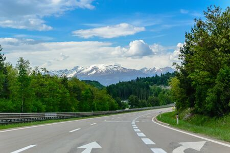 Autobahn or highway in the mountains with clear marking surrounded by vibrant green trees under blue sky. Stunning view and a snow-covered mountain in the background. The Alps, Austria