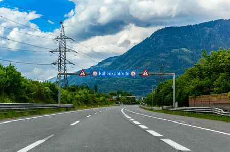 """Alpine highway with road sign """"Hohenkontrolle"""" in German. English translation is """"height control"""". High voltage line and green trees near the road and mountains in the background. The Alps, Austria Stock Photo"""