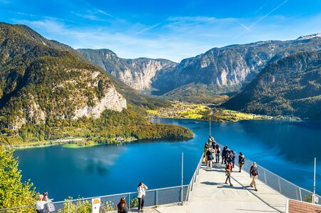 Hallstatt, Austria - OCT 2018: Tourists take photos and enjoy the view of the mountains and lake Hallstatter See from the World Heritage View Point. Popular tourist destination in Austrian Alps.
