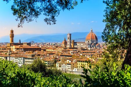 Florence, Italy: view on old town with famous tourist attractions Duomo Cathedral of Santa Maria del Fiore, Campanile and Palazzo Vecchio from Michelangelo square at sunset, framed with green trees 写真素材