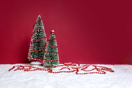 Christmas holiday theme with two small Christmas trees decorated with red beads string on snow against red background. Merry Christmas and winter concept. Copy-space for text. Standard-Bild