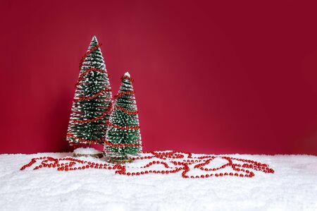 Tema delle vacanze di Natale con due piccoli alberi di Natale decorati con una stringa di perline rosse sulla neve su sfondo rosso. Buon Natale e concetto di inverno. Copia-spazio per il testo.