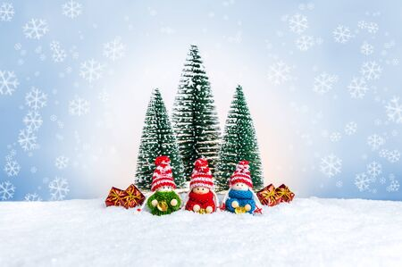 Knitted dolls as small children in colorful sweaters holding bells near fir trees and presents. Cute Christmas figures as a handmade holiday decoration against festive background with snowflakes.