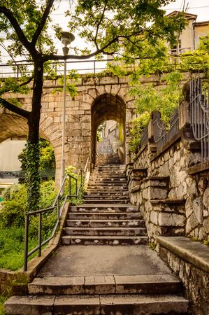 Lower part of Petra Stube, or Petar Kruzic staircase, or Trsat stairway in Rijeka, Croatia with arch and railway bridge. Stone steps lead between house walls up the hill to Trsat Sanctuary