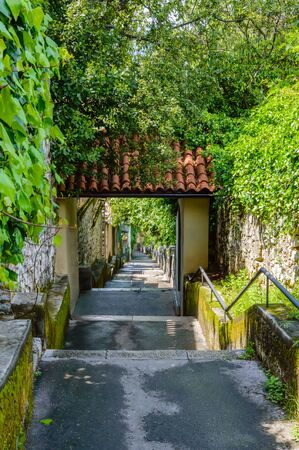 Petra Stube, or Petar Kruzic staircase, or Trsat stairway in Rijeka, Croatia. Trsatske Stube with arch and stone steps leading up the hill to Trsat Sanctuary between house walls covered with ivy