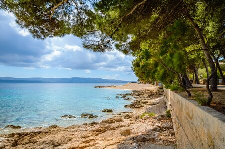 Coastline in Bol, Brac island, Croatia. Scenic view with pine trees, mountains and turquoise water of Adriatic Sea on sunny day. Famous tourist destination near Zlatni Rat or Golden Horn beach Reklamní fotografie