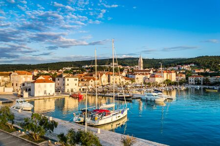 Supetar on Brac Island near Split, Croatia. Small seaside town with promenade and harbor with white boats, palm trees, cafes, houses and church. Tourists walk the street on sunny day at sunset