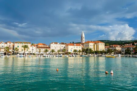 Supetar on Brac Island near Split, Croatia. Small seaside town with promenade and harbor with boats, palm trees, cafes, houses and church. Tourists walk the street on sunny day