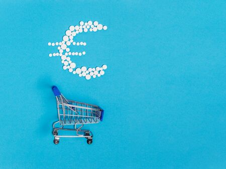 White pills in euro sign shape over shopping cart on blue background. Pharmaceutical concept of medical expenses and prices for medicine, medication or illness treatment costs Stock fotó