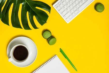 Vivid workspace with keyboard, notebook, pen, cup of coffee, green macarons and monstera leaf on yellow background. Home office, freelance work or blogging concept. Flat lay, top view with copy space