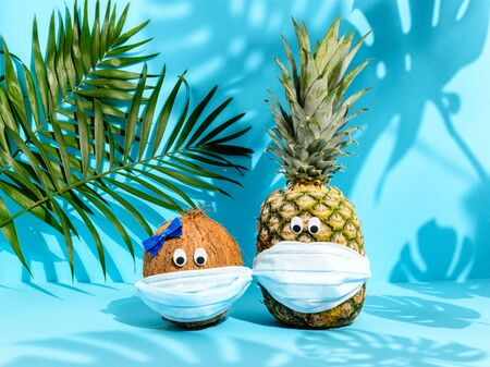 Cute fruit couple coconut and pineapple with eyes in medical masks among palm leaves on blue background. Strong tropical shadows. Hawaiian vacation during Coronavirus pandemic. Summer 2020 concept
