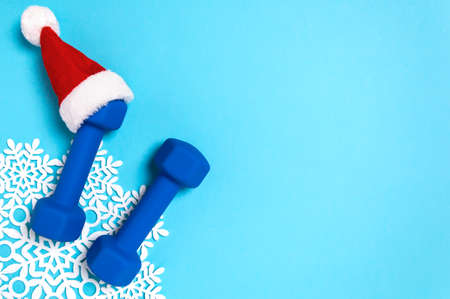 Christmas sport flat lay with dumbbells in red Santas hat on blue background. Christmas and new year holiday concept for fitness, workout and healthy lifestyle. New year resolution to exercise more.