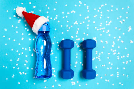 Christmas sport flat lay with dumbbells and water bottle in red Santas hat on blue background with snowflakes. Christmas and new year holiday concept for fitness, workout and healthy lifestyle